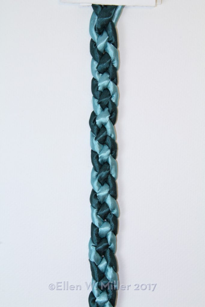 Use two colors in a four strand flat braid to produce a barber pole patterned braid.