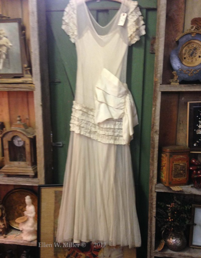 antique, white wedding dress againsta green door.