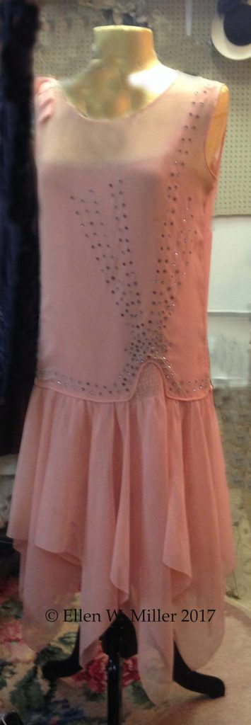 A salmon colored flapper dress embellsihed with crystals.