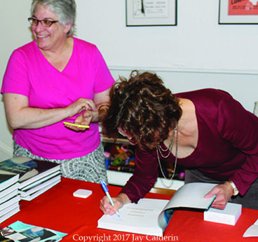 Me bent over to sign a book and Martha using my phone & Square to sell the books.