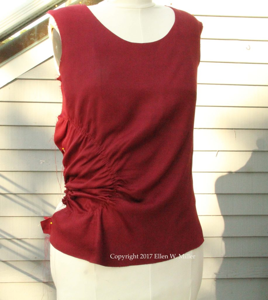 Burgundy top front pinned to dress form with a few rows of gathering stitches on the right