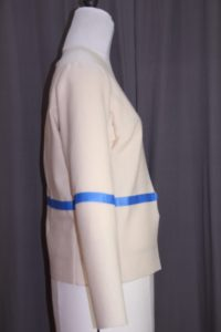 A white wool jacket is on a dress form. Blue painter's tape has been applied at the waistline and at the same level on the sleeves.
