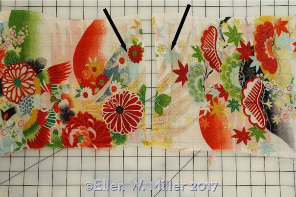 Kimono sleeve flat on worktable showing cleaner fabric with arrows pointing to dirt on the line along the old seam line