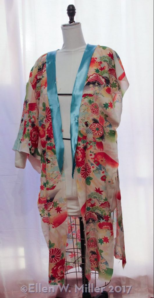 A piece of light teal polyester draped on the kimono as a possible collar fabric