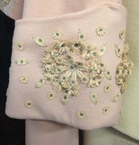 The pink cuff embellsihed with off white crochet work, cyrstals and tiny nailheads.