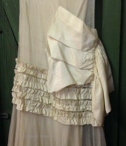 a close up of the white dress: the ruffles along the hip line and the big bow at the waist