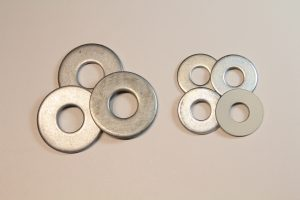 3 large meatl washers on a work table with 4 smaller washers nearby. I use the washers as weights.