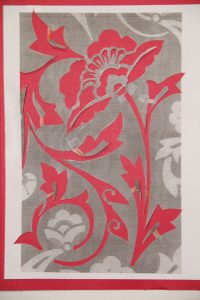 The stencil cut out with red paper behind to make the stencil visible.