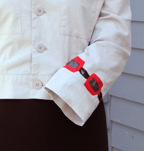 Cuff on tan jacket with Reverse Applique in red, black, silver and black lace.